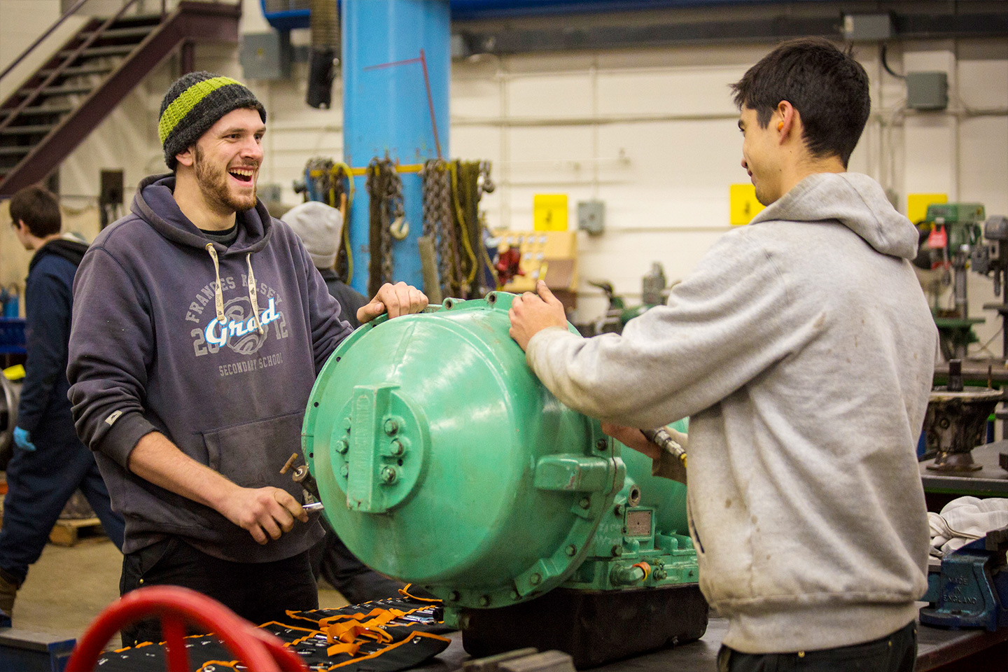 Automotive Service Technician Foundations students smile as they work on an genine