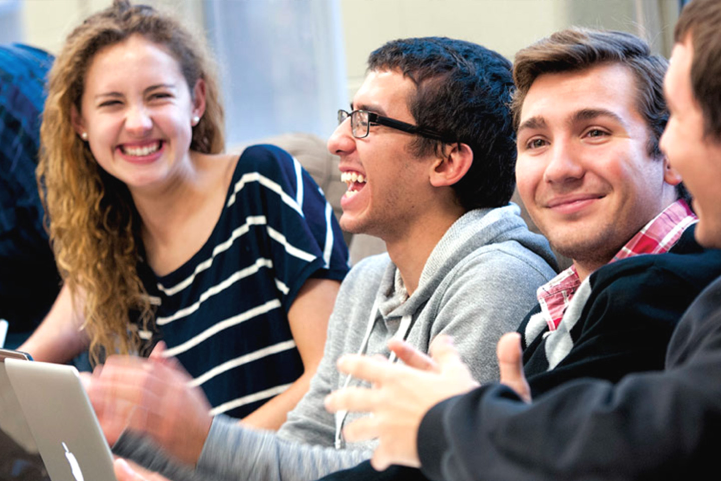 A group of students laughing with each other in class