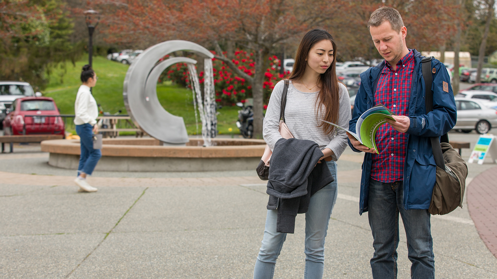 A pair of students chat in front of a large fountain in the shape of the Camosun logo.
