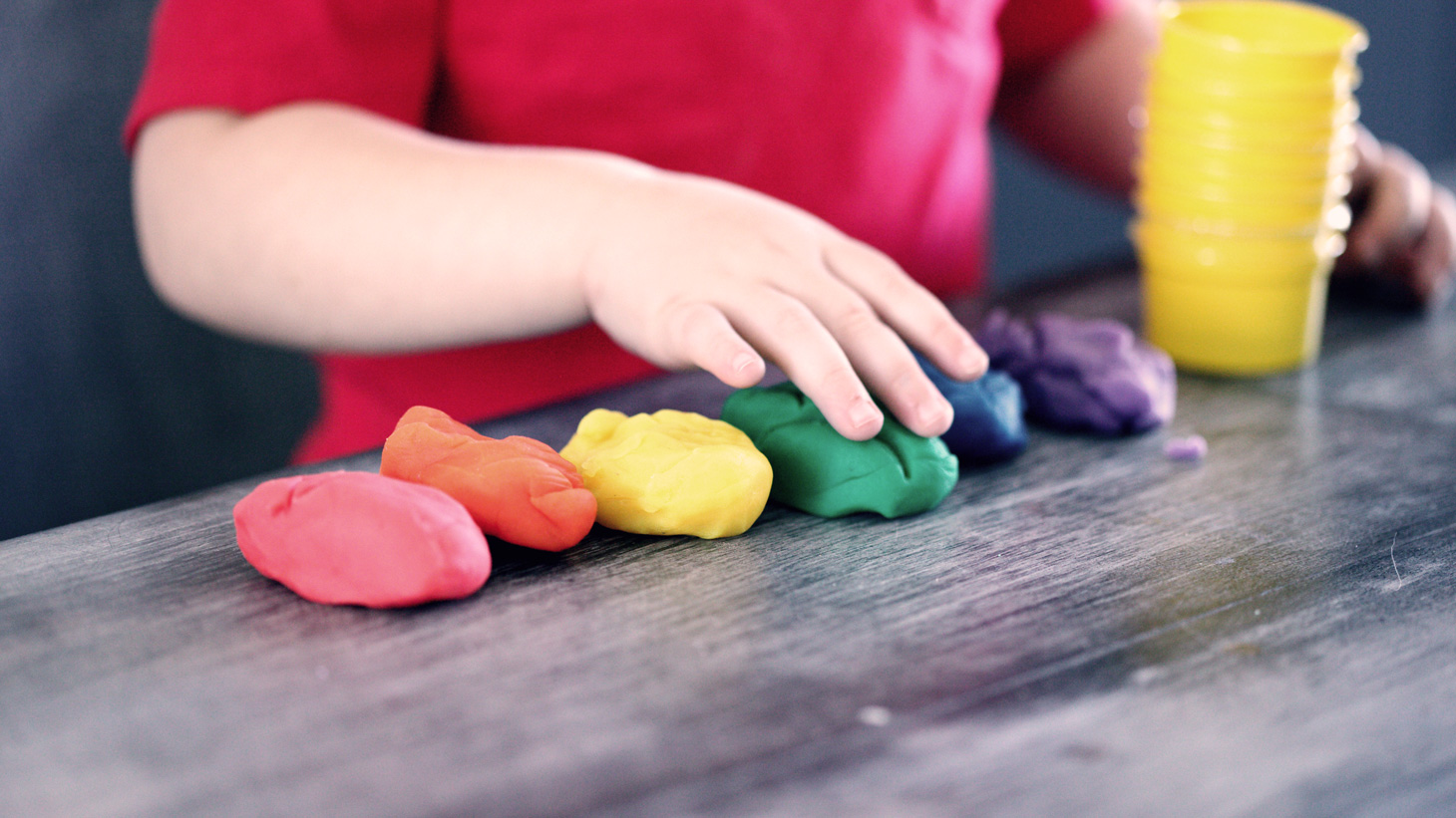 a toddler plays with a  rainbow of playdough