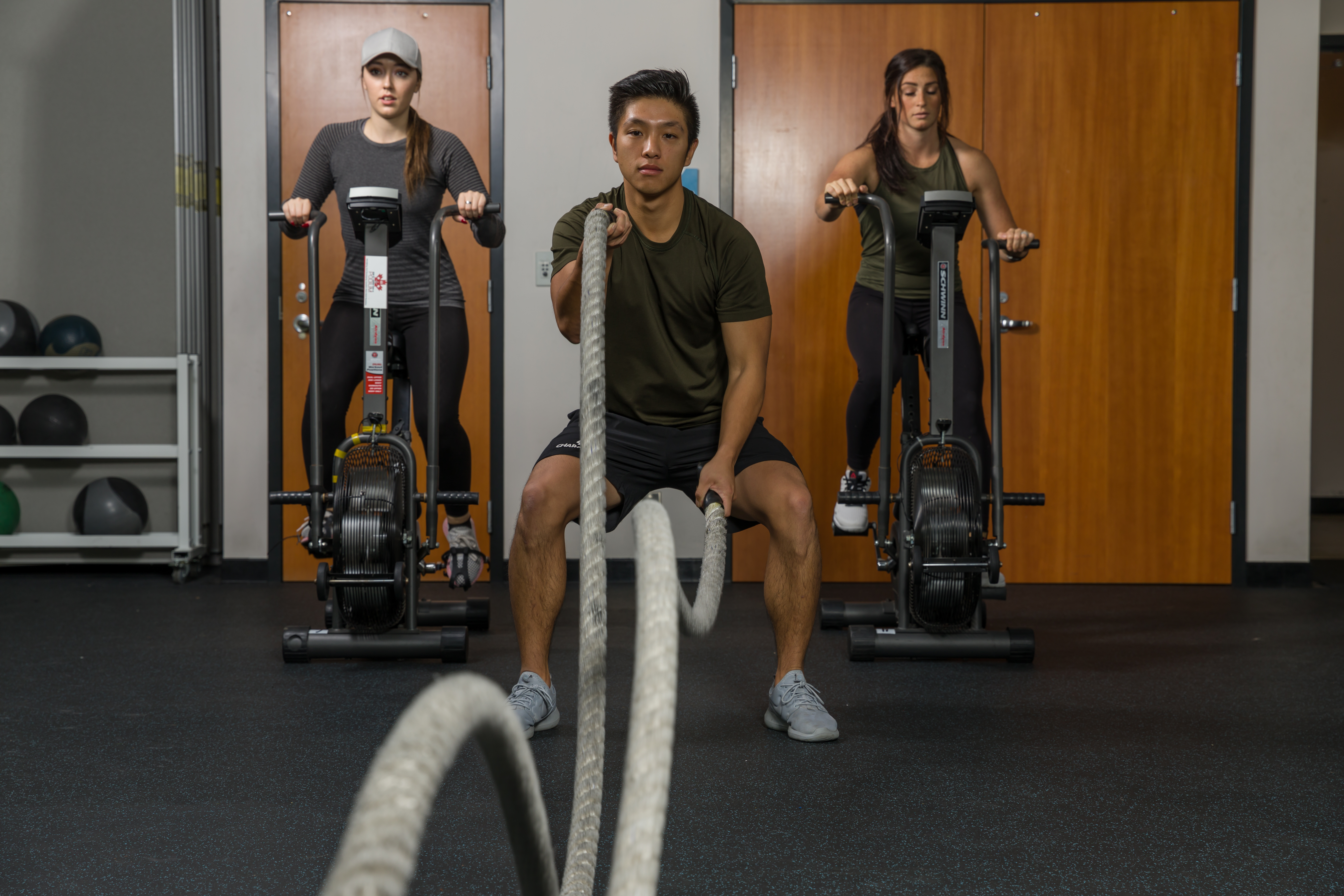 Two students using exercise equipment and one using ropes